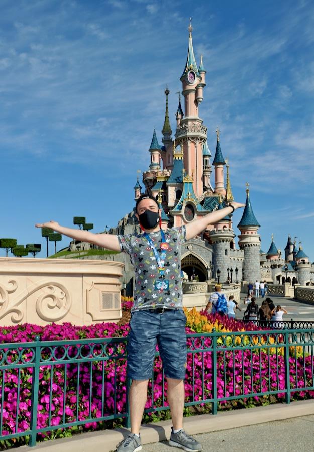 Chico con los brazos abiertos delante del castillo de Disneyland Paris llevando una mascarilla