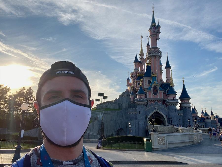 Chico delante del castillo de Disneyland Paris llevando una mascarilla