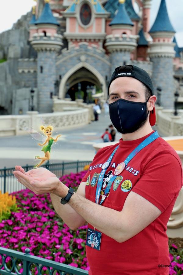 Chico posando delante del castillo de Disneyland Paris con Campanilla sobre sus manos