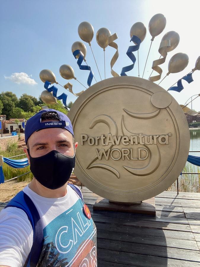 PortAventura chico con mascarilla delante de decoración del 25 aniversario